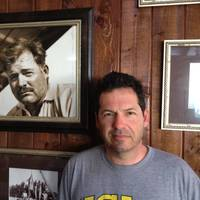 ohn Hemingway poses next to photo of grandfather Ernest Hemingway at the Bimini Big Game Club Resort.